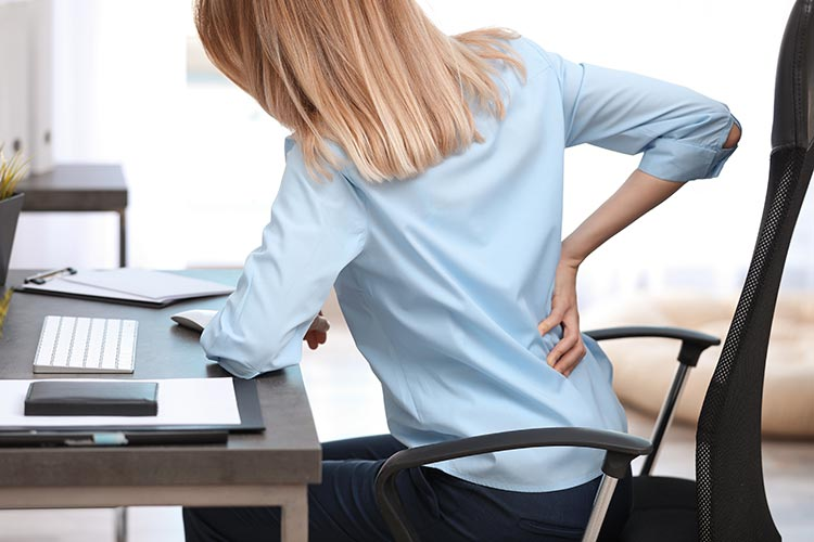 Young woman suffering from back pain in office Atlanta, GA